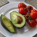 Halbierte Avocado mit Schale und Kern neben Cherrytomaten an Strauch auf weißem Teller
