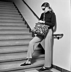 Megan 4 (neohypofilms) Tags: series retro fashion style fun 70s pants slacks shades glasses tall long legs flats mules slippers clogs girl model actress talent bw hasselblad blackandwhite 120 medium format film cinema concept conceptual art stairs steps shoes purse handbag