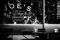 Cup o' joe (Kieron Ellis) Tags: people man boy coffee cafe window reflections chairs lights light contrast shadow table candid street blackandwhite blackwhite monochrome