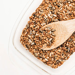 Top view of homemade seeds granola in white bowl and wooden spoon thumbnail