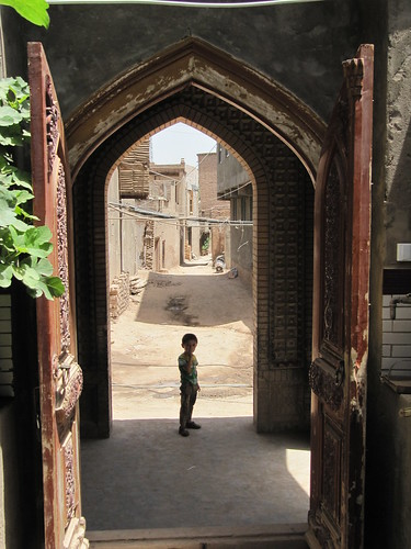 A boy at the entrance of a mosque in old city of Kashgar, Xinjiang, China