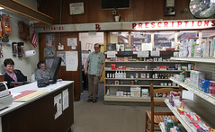Carpenter leans against the door frame that separates the front of the store from the pharmacy in the back.