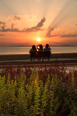 Watching the day slip away (Through_Urizen) Tags: category erdek kapidag places seascape sunset turkey canon canon70d canon1585mm outdoor promenade bench seat photography camera sitting friends chatting sunse clouds sky water sea colorful colourful bay turkiye marmarasea coastal coastline plants planted