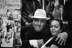 street  portrait (eye contact) (mare_maris) Tags: man woman laterna ανδρασ γυναίκα λατέρνα streetphotography streetportrait street blackandwhite people urban city famous artist entertainer athens greece europe husbandandwife couple together togetherness men women male female person affection latern aged embracing hugging love support outdoors old older mature family lady maturity faces husband wife lifestyle portraiture glance streetlife face eyes expression mood feeling emotion atmosphere character hat style stylish texture documentary depthoffield bokeh human humanity life living society culture nikon maremaris