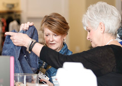 Linda Edmiston (left), 65, nurse anesthetist, from Greensboro, Georgia, and  Merchant (right) look at a scarf together that is sold in Maggie Lane. Edmiston was just in the store the day before, and she returned the next day.