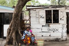 Next to the saloon (RicardMN Photography) Tags: saloon woman arusha manyara masais ngorongoro serengeti tanzania tarangire fruit seller africa road street photography umbrella bicycle man people streetphotography awards project series ricardmn ricardmnphotography culture contrast rural primitive basket bag