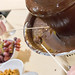 Weintrauben an Spießen in einem Schokoladenbrunnen