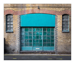 The Built Environment, East London, England. (Joseph O'Malley64) Tags: thebuiltenvironment newtopography newtopographics manmadeenvironment manmadestructure building structure victorian victorianbuilding urban urbanlandscape architecture architecturalfeatures architecturalphotography britishdocumentaryphotography documentaryphotography northlondon london england uk britain british greatbritain brickwork bricksmortar cement pointing glazedbricks brickarches frostdamage waterdamage airpollutiondamage acidraindamage hygroscopicsaltsinbrickwork woodenwindowframes blockedwindows brokenwindows doorway door woodendoor woodwork entrance exit woodenpanel woodenpanels plywoodpanels spotlight lighting conduit electricalconduit concrete tarmac doubleyellowlines noparkingatanytime parkingrestrictions incline gradient fujix fujix100t accuracyprecision