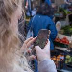 Eine Frau macht ein Foto mit ihrem iPhone von Gemüse auf einem Markt in Rom thumbnail