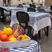 Schale mit Kürbissen, Zitronen, Karotte und Salat auf Tisch auf der Terrasse eines Restaurants in Rom mit schwarzen Plastikstühlen und blau-weiß karierten Tischtüchern