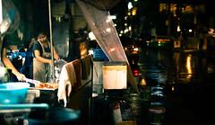 At the Corner (dlerps) Tags: bkk bangkok city daniellerps lerps sony sonyalpha sonyalpha99ii tha thai thailand urban lerpsphotography metropolitan woman female working street streetphotography washing rain wet wetseason sukhumvitsoi57 carlzeiss sukhumvit thonglo night evening darkness asian asia streetfood foodstall planart1450 apron carlzeissplanar50mmf14ssm cooking happyplanet asiafavorites