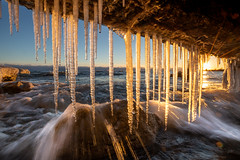 a winter's sunset (Marc McDermott) Tags: lakeontario icicles sunset wave breaking shore winter cold freezing ontario canada rock water sky clear starburst