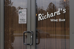 The sign for Richard's Wine Bar is located on the door the to restaurant.