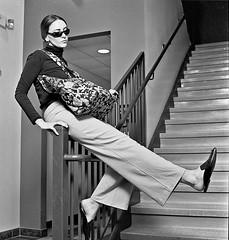 Megan 2 (neohypofilms) Tags: series retro fashion style fun 70s pants slacks shades glasses tall long legs flats mules slippers clogs girl model actress talent bw hasselblad blackandwhite 120 medium format film cinema concept conceptual art stairs steps shoes purse handbag