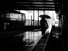 Rainy days can be moody... (明遊快) Tags: bw woman japan lines railway train wet alley road umblella dark 高架下 傘 雨