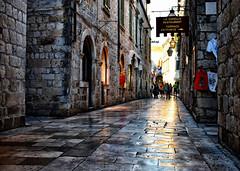 Pavements 2 (Jocelyn777) Tags: streets roads buildings architecture stones cobblestones stonehouses light lightreflections pavementreflections sunset evening shops people dubrovnik croatia balkans travel