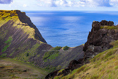 Easter Island - the crater of Rano Kua Vocano above Pacific Ocean in a sunny day. (baddoguy) Tags: above adventure ancient backgrounds beauty in nature chile cliff cloud sky color image copy space day famous place high angle view hill horizon horizontal international landmark local moai statue rapa nui moss mountain ridge mystery national park no people nonurban scene outdoors pacific coast ranges islands ocean photography reflection risk rock object rural sea south america summer tourism travel destinations unesco world heritage site volcanic crater volcano