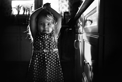 An Impromptu Kitchen Portrait (Kapuschinsky) Tags: blackandwhite monochrome child childhood candid lifestyle indoors naturallight lensbaby seeinanewway burnside35 sonyalpha sonya900 kapuschinsky polkadots dress emotive moody portrait portraiture curls windowlight backlit backlight