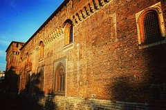 Castello Sforzesco di Milano, Milano, Italia Another angle of this castle as we walked around it on our way to dinner with family. The late afternoon sun makes it bricks glow and highlights all the crenelations, mortar joints and scaffold holes in its ext (dewelch) Tags: