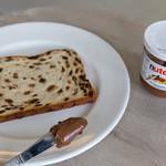 Hand streicht Nutella mit Messer auf Brot mit Früchten und Rosinen thumbnail