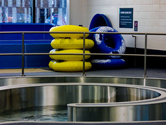 Hydro Slide Exit (Steve Taylor (Photography)) Tags: rubberring pool railing architecture design fence silver yellow blue metal tile water liquid newzealand nz southisland canterbury christchurch northnewbrighton shiny rubber swimmingpool taioraqeiirecreationandsportcentre