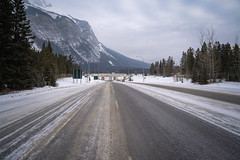 View of an icy snowy road in Banff Alberta Canada, leading onto the Trans-Canada Highway with the Canadian Rockies in background (m01229) Tags: rock nature glacier snow trees summer national road tree peak scenic outdoors canada canadianrockies view sky landscape winter range lake nationalpark mountains banff outdoor landscapes trip rocky clouds canadian cold blue parkway scenery beautiful highway cloud alberta forest rockies park travel tourism wilderness mountain