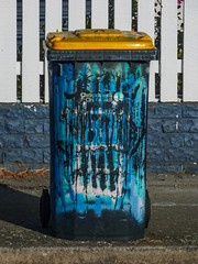 The Recycle Monster (Steve Taylor (Photography)) Tags: recycle bin monster teeth graffiti fence road black blue white yellow scary frightening spooky plastic newzealand nz southisland canterbury christchurch newbrighton stripes