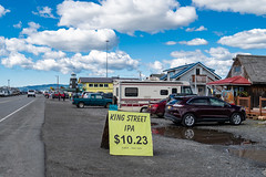 AUGUST 3 2018 - HOMER, AK: Shops and restaurants along the Homer Spit during summer in Alaska (m01229) Tags: alaska restaurants nature katchemakbay image land background sea summer drone stores scenic outdoors america shops homer shopping flying outdoor spit cold kenaipeninsula overheadview blue sky bars homerspit bay mountains kachemakbay ocean barrierisland tourism touristattraction mountain