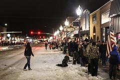 Crowd Gathers for the Christmas Parade (wyojones) Tags: wyoming cody sheridanavenue snow annualchristmasstrollandparade christmas parade street crowd snowballfight people flag stores wyojones
