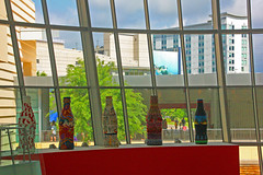 Inside the World of Coca Cola Museum, Looking Out, Atlanta GA (gg1electrice60) Tags: cocacola johnspemberton inventedcocacolain1886 cocacolamuseum worldofcocacola 121bakerstreetnw atlanta georgia ga fultoncounty unitedstates usa us america nearhiltongardeninnhotel nearcentennialolympicpark centennialolympicpark smallpark pharmacistjohnstithpemberton cocacolabottlingcompany atlantametropolitanarea downtown downtownatlanta cityofatlanta fancycokebottles decoratedcokebottles paintedcokebottles lookingoutthewindow embassysuiteshotel buildings architecture georgiaacquariumbuilding georgiaaquariumbldg peopleoutside touristsoutside trees bluesky partycloudy artisticallydecoratedbottles display giftshop store