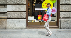 Milan 08 (Peter.Bartlett) Tags: bag eyecontact shopfront reflection city urbanarte colour peterbartlett urban candid walking wall woman streetphotography shopwindow lunaphoto sign people facade ricohgr milano lombardia italy it