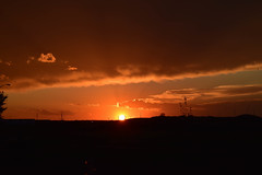 Powerful orange glow sunset (darletts56) Tags: sky sun sunset glow ray rays clouds cloud tree trees field fields prairie pole poles post posts highway road vehicale lights light building buildings evening grey white orange black silhouette saskatchewan canada power line bird lamp