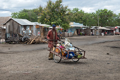 Recycling (RicardMN Photography) Tags: recycling traffic wheel arusha manyara masais ngorongoro serengeti tanzania tarangire fruit seller africa road street trafic photography umbrella bicycle man people streetphotography awards project series ricardmn ricardmnphotography fruits culture contrast rural primitive head workshop men