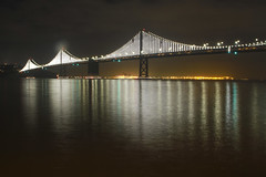 San Francisco: The Bay Bridge Illumination (rocinante11) Tags: sanfrancisco california unitedstates baybridge bridge night light ambient ambientlight longexposure timedexposure dark city water reflection