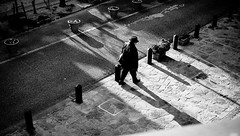 Long Shadow at dusk (明遊快) Tags: bw man street urban outerwear sunlight shadows hat walk candid dusk evening city