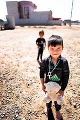 Yazidi child and his teddy bear (Giulio Magnifico) Tags: sinjar 28mm iraq boy happy mosul da3sh kurdistan arabic camp iraqi deepsoul children teddybear happiness yazidi genocide curiosity leicaq middleeast civilwar isis leica child
