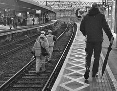 It's Quicker By Rail (tcees) Tags: stratfordmainlinestn london stratford e15 platform railwaylines umbrella gantry signs x100 fujifilm finepix urban man woman people window signal streetphotography street pillars bw mono monochrome blackandwhite uk hat hardhat sky cables roof fence shadows pattern tools railway curve