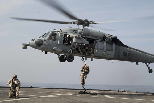 U.S. Marines fast-rope onto the flight deck during a simulated visit, board, search, and seizure mission aboard USS Rushmore.