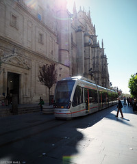 Tram (peterphotographic) Tags: p3140430edwm tram olympus em5mk2 microfourthirds ©peterhall seville sevilla espina spain andalusia travel train transport publictransport city cityscape urban flare intothelight street sevillecathedral cathedral shadow europe