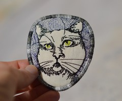 saint kitty pin (Danny W. Mansmith) Tags: oneofakind handmade originalart threaddrawing embroidery sewing stopmotionsewing dannymansmith wwwdannymansmithetsycom details satinstitch burienwashington wearableart fabricpin brooch art fiberart