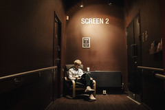 Screen 2 (markfly1) Tags: man waiting reading cinema screen two 2 lines leading chair cup tea drink candid street photo brown earthy colour deep maroon red trainers casual foot wear blond blonde hair door doorway entrance pictures walls nikon d750 35mm manual focus lens
