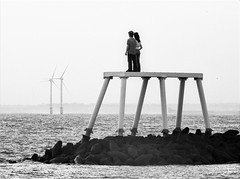 Couple Statue and a Couple of Wind Turbines (Gilli8888) Tags: nikon p900 coolpix northumberland newbigginbythesea newbiggin northsea beach sand coast coastal shore seaside seascape sun dawn sea water marine blackandwhite rocks couplestatue statue art publicart sculpture seanhenry turbines windturbines two couple linear platform