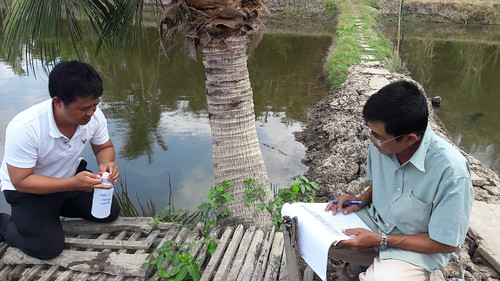 Can Tho University researcher and farmer engaged in water-quality monitoring in Vietnam. Photo by Olivier Joffre.