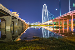 Dallas Doubled (tquist24) Tags: dallas hdr margarethunthillbridge nikon nikond5300 outdoor ronaldkirkpedestrianbridge texas trinityriver architecture bridge bridges city cityscape flag flagpole geotagged grass light lights longexposure moon reflection reflections river sky skyline skyscraper skyscrapers urban water unitedstates bluehour