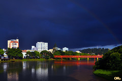 Shy rainbow in a dark sky (Otacílio Rodrigues) Tags: arcoiris rainbow pontes bridges prédios buildings rio river água water nuvens clouds céu sky reflexos reflections árvores trees grama grass urban arquitetura architecture resende brasil oro natureza nature supershot