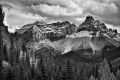 Cathedral Crags Portrait (Black & White, Yoho National Park) (thor_mark ) Tags: nikond800e day3 triptoalbertaandbritishcolumbia cathedralcrags lookingse yohovalley capturenx2edited colorefexpro yohonationalpark outside nature landscape overcast rockymountains canadianrockies mountains mountainsindistance mountainsoffindistance hillsides hillsideoftrees evergreens trees yohovalleyroadarea alongyohovalleyroad cathedralmountain southerncontinentalranges banfflakelouisecorearea bowrange silverefexpro2 blackwhite portfolio project365 ideasigotfromothers mountainside britishcolumbia canada