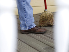 Hillman sweeps the wooden floors of the porch.