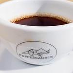 Kaffee in weißer Tasse mit Aufschrift Kaffeesaurus mit Untersetzer auf Holztisch mit Stuhl im Hintergrund thumbnail