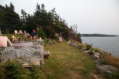 Trinity Deck (peterkelly) Tags: digital canon 6d northamerica canada newfoundlandlabrador cavendish chairs chair table flames flame lit fire heat shoreline shore coastline coast trees deck lobstertraps water trinitybay rocks boulder