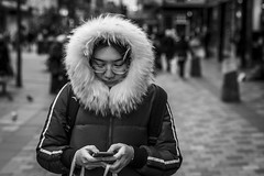 Ring of Fur (Leanne Boulton) Tags: portrait people urban street candid portraiture streetphotography candidstreetphotography candidportrait streetportrait streetlife modernliving woman female girl face expression mood feeling mobile phone smartphone screen technology connection socialmedia fur furry hood cold winter weather dark tone texture detail depthoffield bokeh naturallight outdoor light shade city scene human life living humanity society culture lifestyle canon canon5dmkiii 70mm ef2470mmf28liiusm black white blackwhite bw mono blackandwhite monochrome glasgow scotland uk